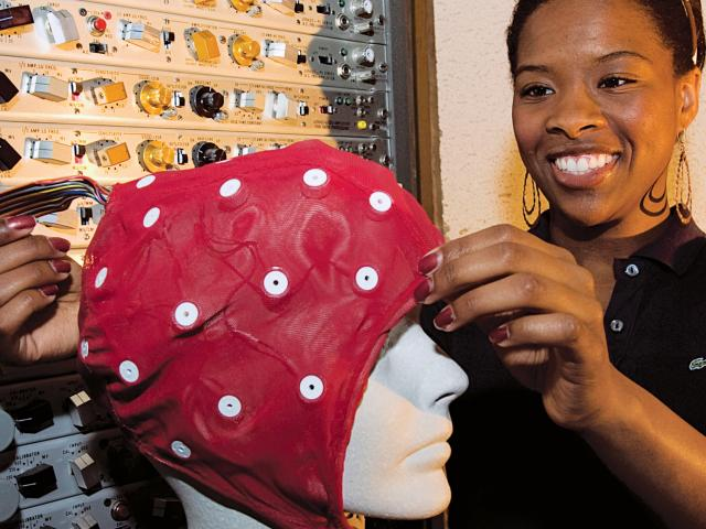 Student placing a cognitive cap on a mannequin