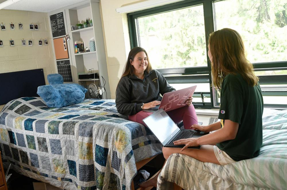 two girls sitting and talking in a dorm room on campus