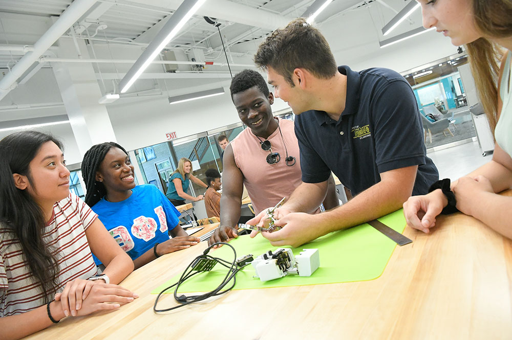 A Clarkson Ignite student worker shows fellow Clarkson students how to use various tools in the Innovation Hub Makerspace.