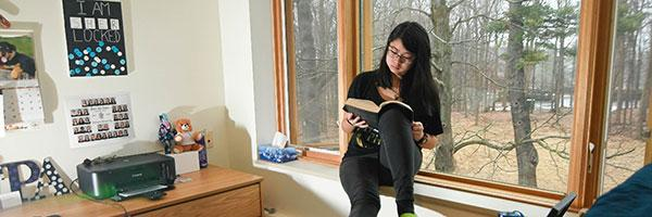 A Clarkson undergraduate student relaxes in a residence hall room on campus