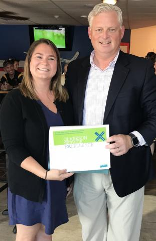Clarkson University New Student Financial Aid Advisor Ashlee Whalen has been named the Employee of the Month for July. Above, Whalen (left) receives her Employee of the Month certificate and pin from Vice President for Enrollment & Student Advancement Brian Grant.