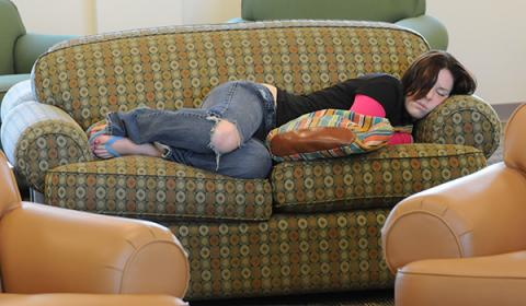 A student sleeping on a couch