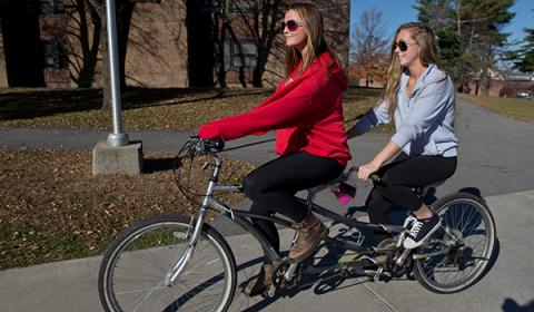 Two female students riding a tandem bike through campus