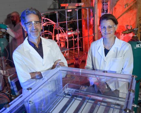 Professors Thomas Holsen and Selma Mededovic Thagard pose in the CAMP lab with the enhanced contact electrical discharge plasma reactor, a novel method for degrading poly- and perfluoroalkyl substances (PFASs).