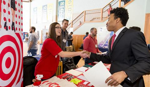 A Clarkson student at the career fair shaking hands with a Target Representative