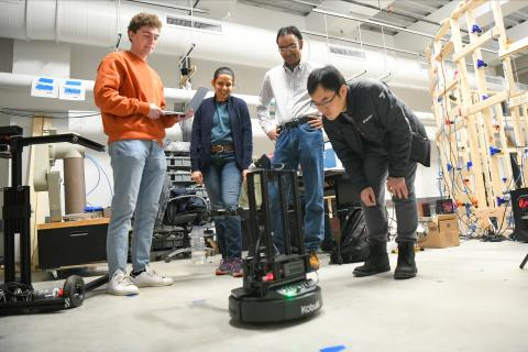 Clarkson faculty members Sean and Natasha Banerjee test their robotics with students