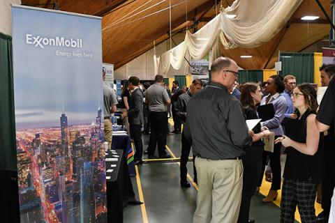 A Clarkson undergraduate student talks to a representative of potential employer ExxonMobil at Career Fair