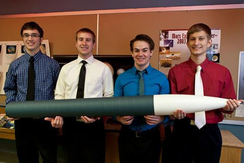 Undergraduate students in Clarkson's Rocket Club show off their rocket