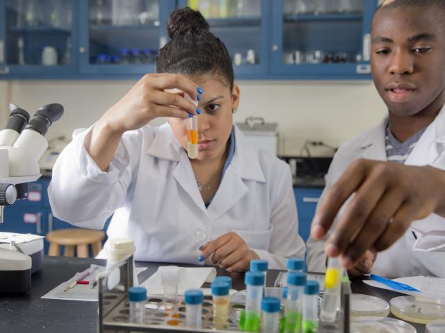 Undergraduates Zoila Urena and Ebuka Ononye in lab coats examining test tubes in a biology laboratory