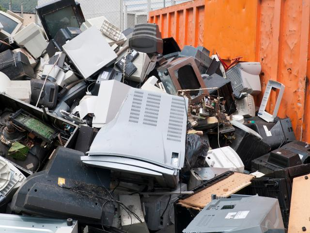 Various electronics in a dumpster