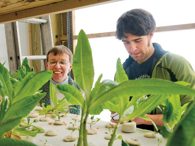 Professor Susan Powers and a student working in the greenhouse