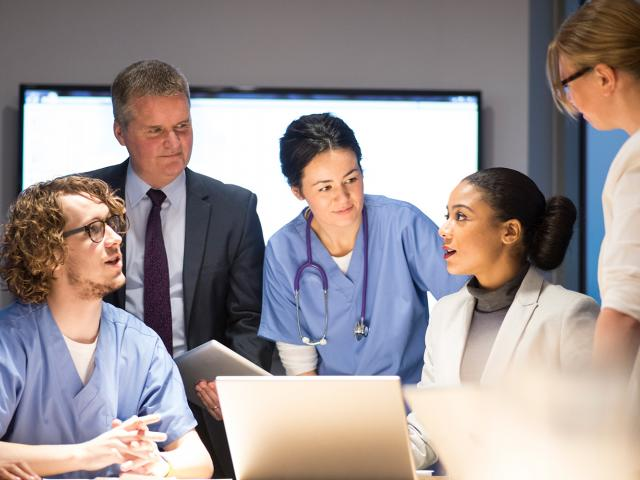 Individuals in a medical setting having a meeting