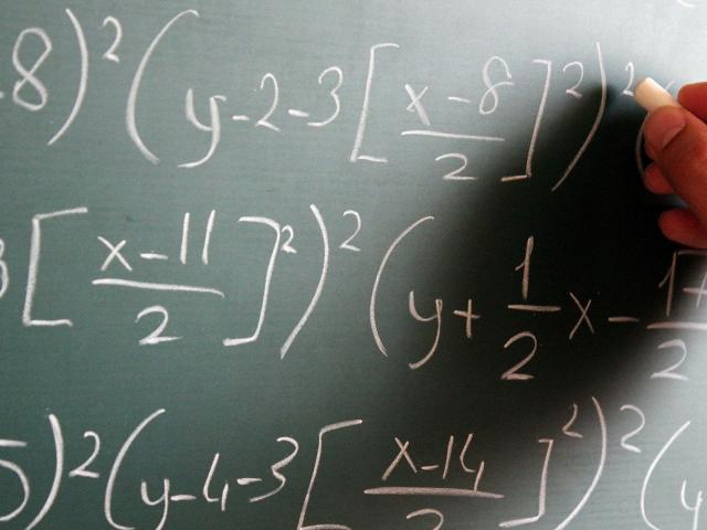 Math formulas being written on a chalkboard