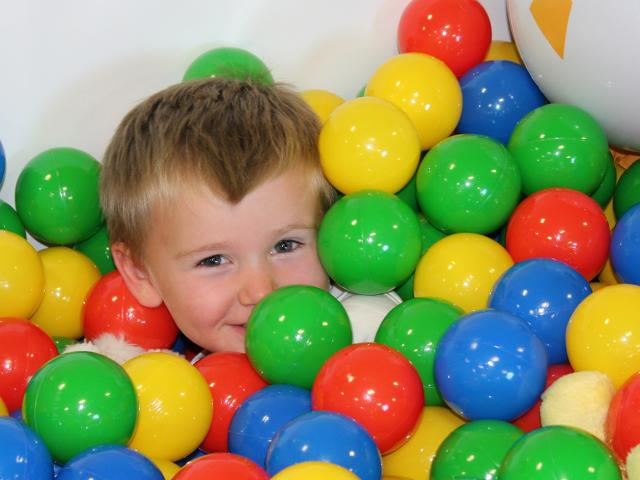 Young child in a ball pit during an occupational therapy session