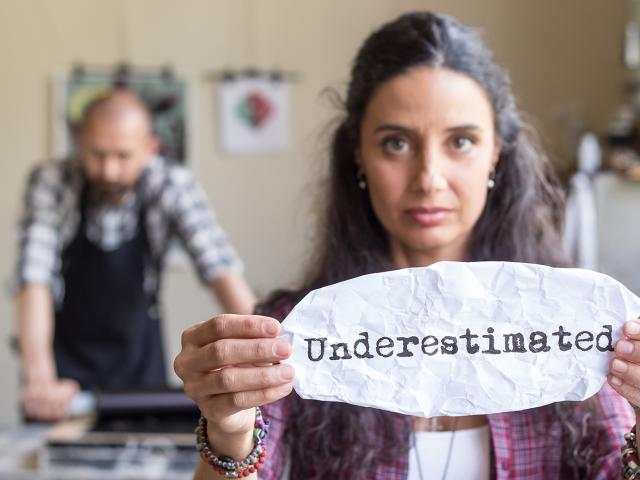 Woman holding up a piece of paper with the words Underestimated written on it with a male in behind her.