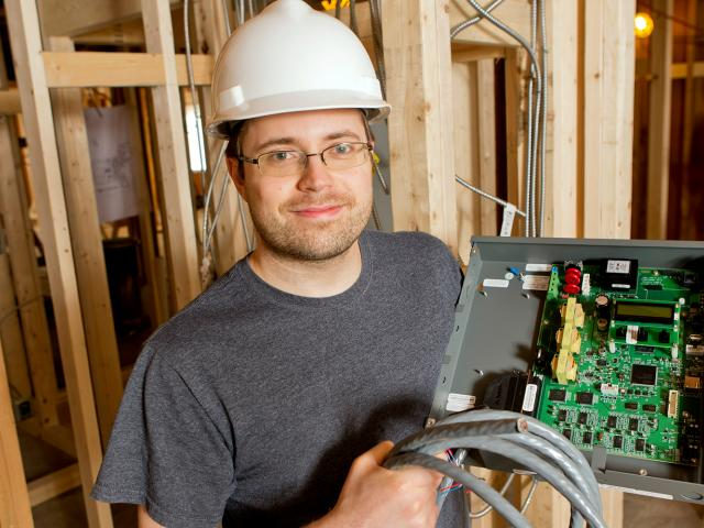 Patrick Wilbur holding the elctrical components for the smart dorm during installation