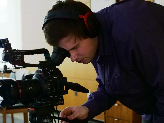 Student, Zach Brunelle using a top level video camera.