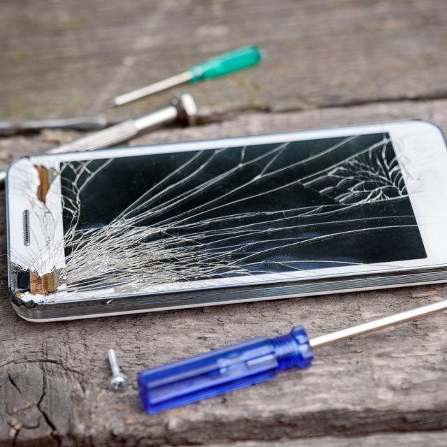 A cell phone with a cracked screen and the tools to fix it